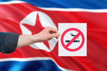 North Korea Health Concept. Hand Holding Paper With No Smoking Sign Over National Waving Flag. Quit Smoke Theme.