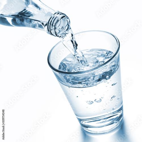 Nalewanie wody do szklanki z butelki ze szkła
