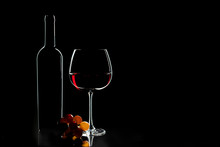 Elegant Red Wine Glass, Wine Bottle And Bunch Of Grapes On The Dark Background.