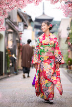 Japanese Girl Walk In Kyoto Old Market And Wooded Yasaka Pagoda With Sakura Flower Background