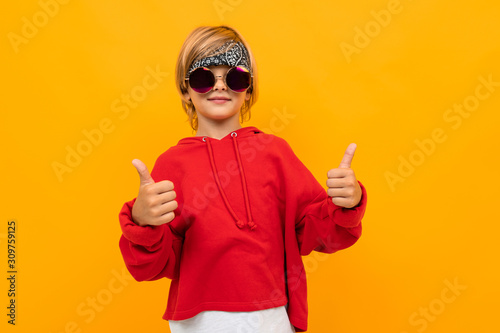 Cuadros en Lienzo  attractive blond boy with a bandana on his head in a red sweater and glasses sho