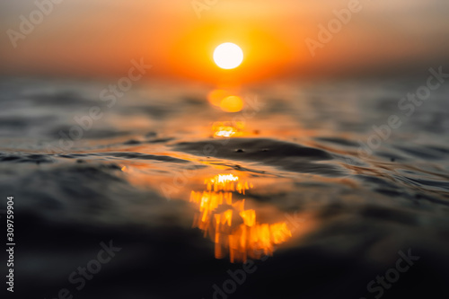 Fototapeta Sunset and waves in ocean. Warmy water texture with bokeh obraz