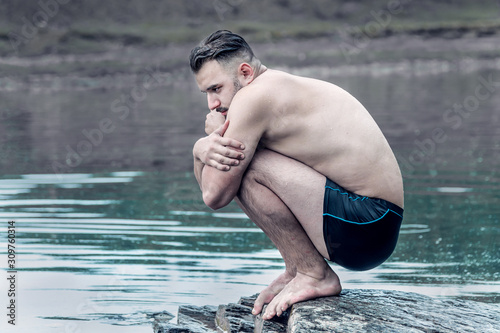 In the middle of the water sits a freezing man in swimming trunks in the fetal position Slika na platnu