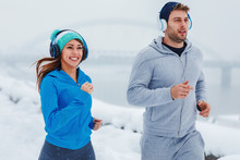 Young Man And Woman Running On A Snowy Day