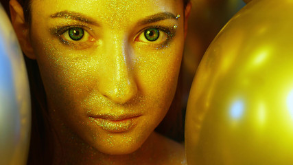 closeup girl face with Golden sequins among the Golden balloons