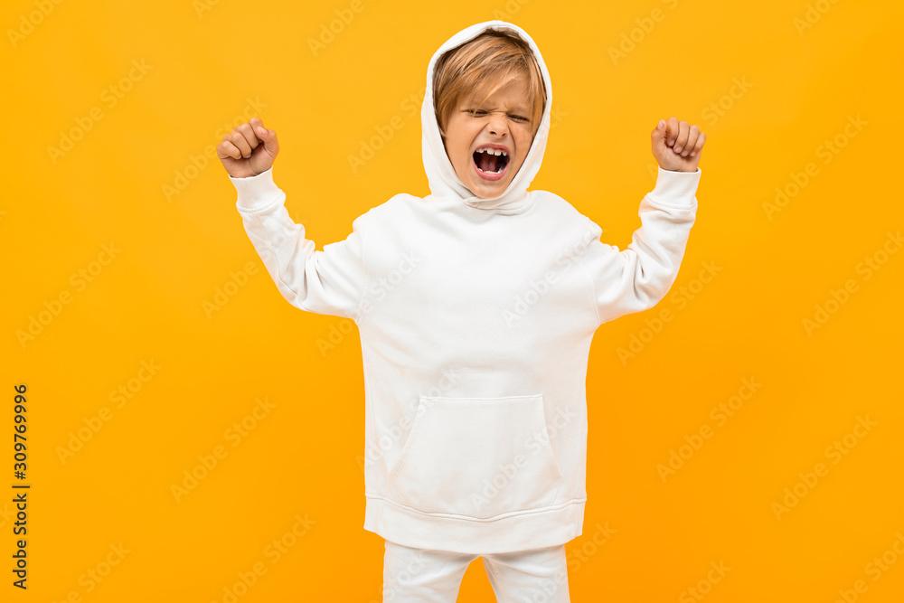 Obraz attractive blond boy in a white hoodie screaming out loud on an orange wall fototapeta, plakat