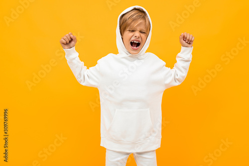 attractive blond boy in a white hoodie screaming out loud on an orange wall