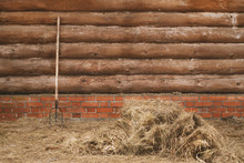 Log Wall With Pitchfork And Haystack. Farmland Background With Copyspace