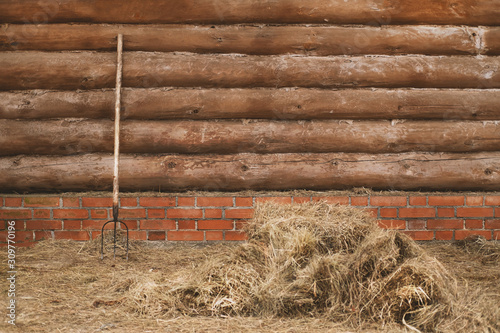 Tablou Canvas Log wall with pitchfork and haystack
