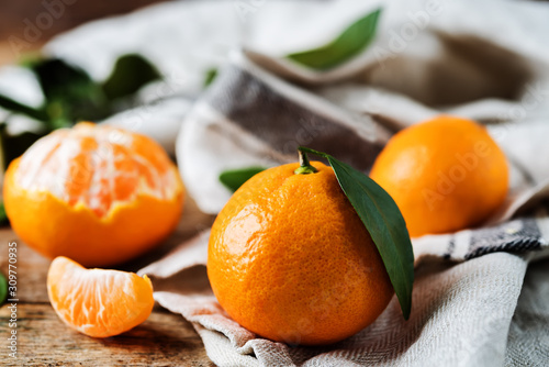 Fototapeta Mandarynki  owoce-mandarynki-z-plasterkami-skorka-i-liscmi