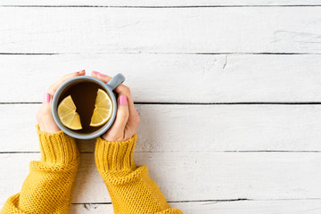 Female hands in warm sweater holding cup of tea with lemon on white wooden table. Top view