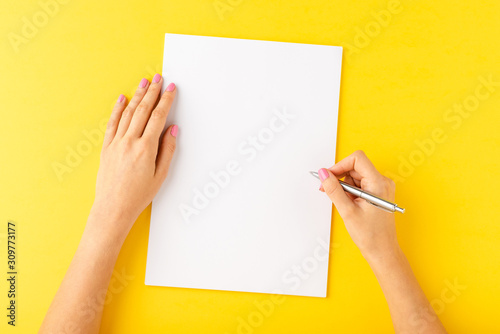 Canvastavla Overhead shot of woman's hands writing on empty white sheet of paper