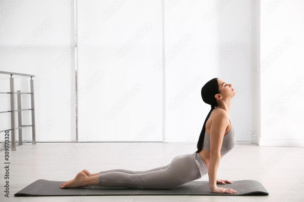 Fototapeta Young woman practicing cobra asana in yoga studio. Bhujangasana pose