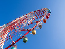 Partial View Of A Ferris Wheel With Multicolored Pods On A Background Of Blue Sky