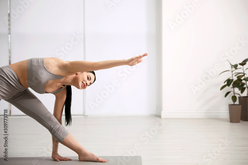 Fotomural  Young woman practicing triangle asana in yoga studio