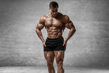 Muscular Man Showing Muscles Isolated On The Wall Background. Strong Male Naked Torso Abs
