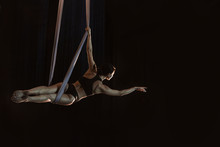 Young Woman Performing Acrobatic Element On Aerial Silk Against Dark Background