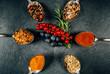 Sechs Löffel mit Gewürzen im Kreis angerichtet und Früchten in der Mitte