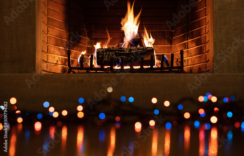 Fotografiet  Christmas burning fireplace and lights, holiday decoration background