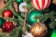 Christmas background tree branch with decorations candy lollipop cane red and green balls, with bokeh light