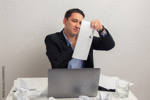 Vászonkép businessman tearing up a paper with a pen . spite