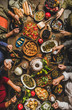 Traditional Turkish celebration dinner at rustic table. Flat-lay of people eating Turkish salads, cooked vegetables, meze starters, pastries and drinking raki drink, top view. Middle Eastern cuisine