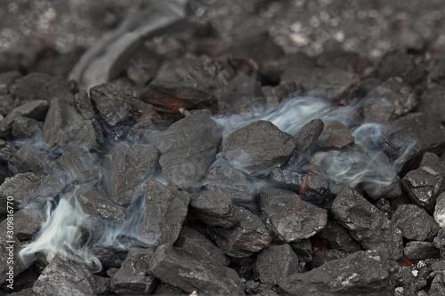 Smoke over the coals of a blacksmith's brazier where the iron horseshoe is annea Wallpaper Mural