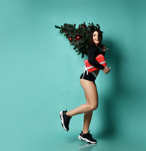 Smiling Sporty Woman Is Running With Christmas Tree On Her Shoulder, Holding Red Presents Gift Box, Looks Back