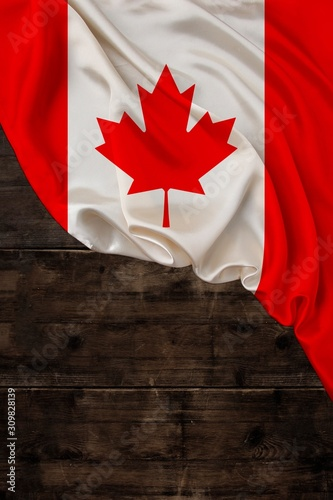 vertical colored national flag of modern state of Canada, beautiful silk, old wood background, concept of tourism, economy, politics, emigration, independence day, copy space, template