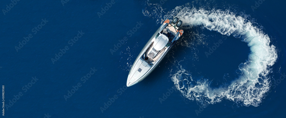 Fototapeta Aerial drone ultra wide top down photo of luxury rigid inflatable speed boat cruising in high speed in Aegean deep blue sea, Greece