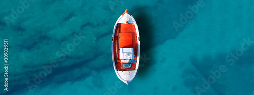 Fotografia Aerial drone top down ultra wide photo of traditional fishing boat docked in wor