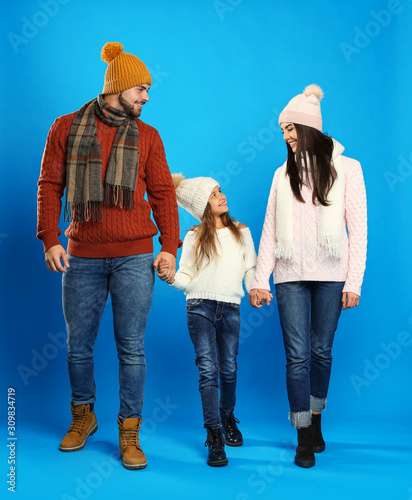 Happy family in warm clothes on blue background. Winter vacation - 309834719