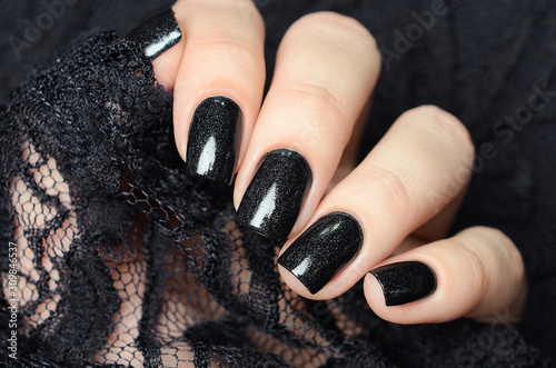 dark blue manicure on a background of black lace