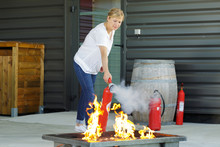 Determined Woman Holding A Red Fire Extinguisher