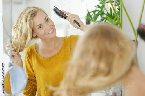 a young woman brushing hair Tablou Canvas