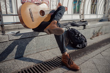 Young Guitarist Sitting And Resting With Guitar Outdoors