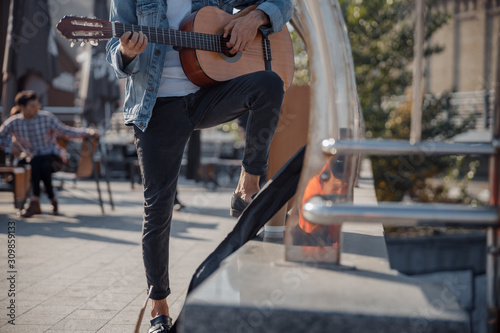 Fototapety, obrazy: Young guy holding guitar and playing on the street