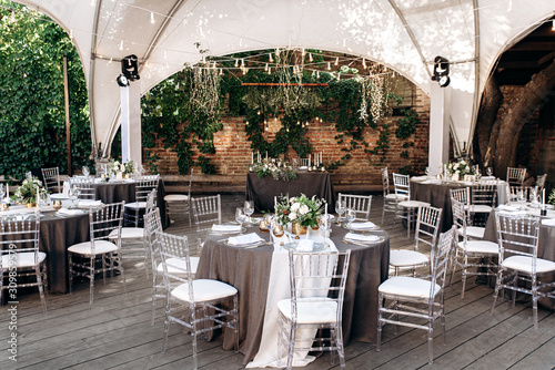 Fototapeta Festive banquet. Round tables which are beautifully decorated with plates, candles and a beautiful composition of flowers and table number in the center obraz