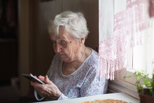 Old Woman Sits With A Smartpho...