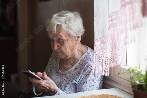 Canvastavla Old woman sits with a smartphone in her hands on the room.