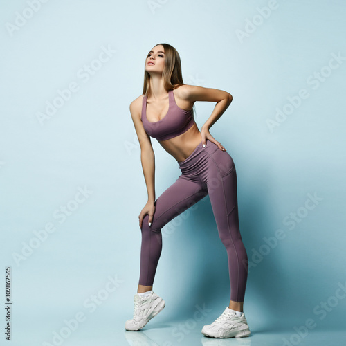 Beautiful sportswoman in sportswear working out doing stretching sports exercise Canvas Print