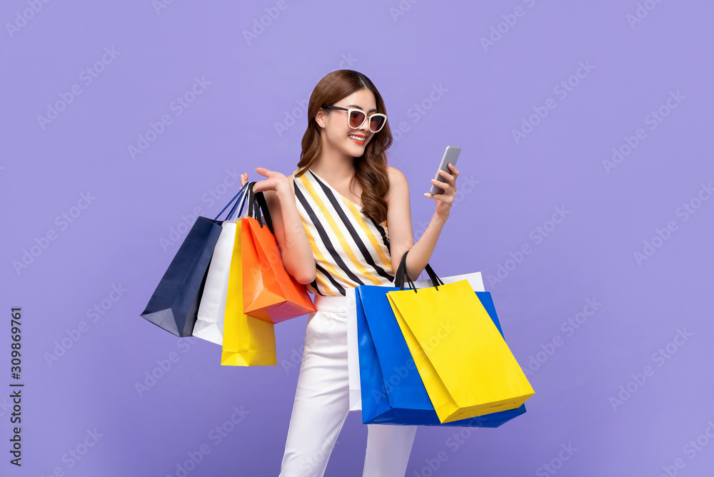 Fototapeta Beautiful Asian woman carrying colorful bags shopping online with mobile phone