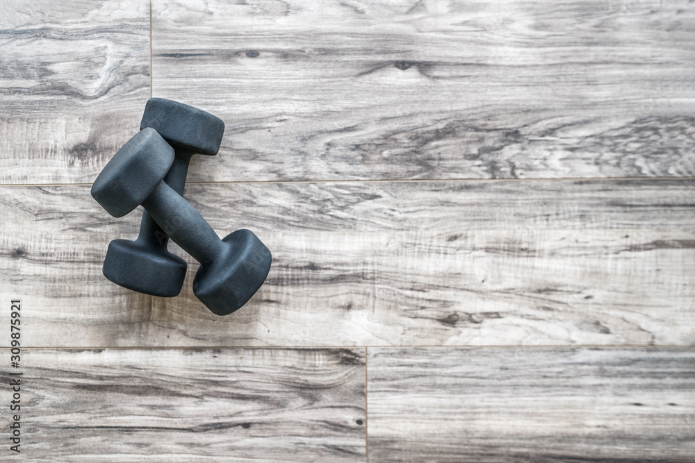 Fototapeta Gym fitness strength training exercise dumbbell free weights top view wooden background with copy space. Active weight loss lifestyle. Home workout.