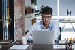 asian businessman woking with laptop and paper work on desk at office.digital workflow online business lifestyle concept.