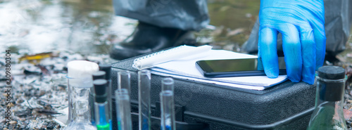close-up of a scientist's hand in blue protective gloves, against the background of a river and test tubes with liquids, puts a mobile phone on a black suitcase for inventory - fototapety na wymiar