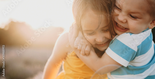 Fototapeta Close up portrait of a lovely little kid embracing with love his sister against sunset. obraz