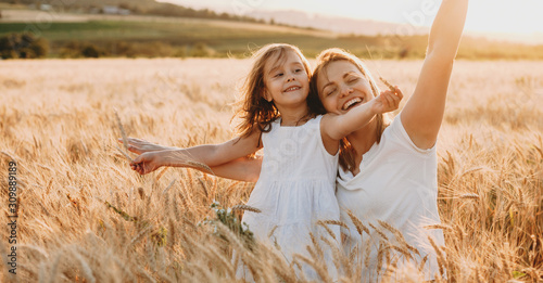 Portrait of a happy young mother and her lovely daughter playing and laughing in a field of wheat Fototapete