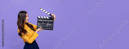 Young beautiful Asian girl holding movie clapperboard Fototapet
