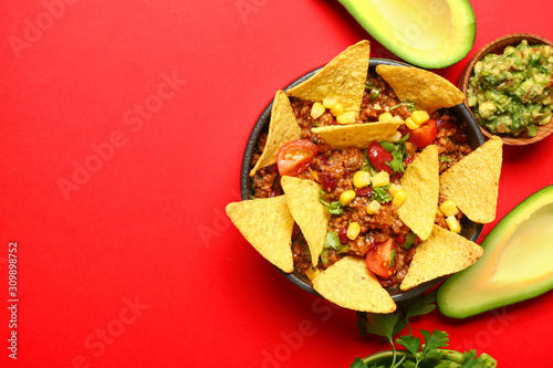 Fotografía Bowl with tasty chili con carne and nachos on color background