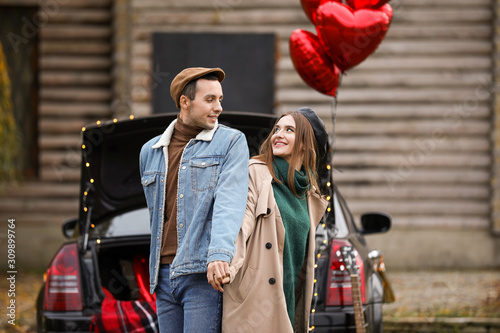 Happy young couple near car outdoors. Valentine's Day celebration Wallpaper Mural